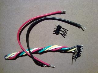 Согнутая гребёнкa со штырьками и семью разноцветными проводами для коммутации